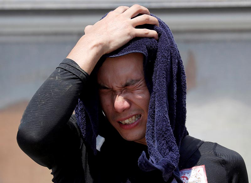 A volunteer, for recovery work, wipes his sweat as he takes a break in a heat wave at a flood affected area in Kurashiki, Okayama Prefecture, Japan, on July 14, 2018. Photo: Reuters