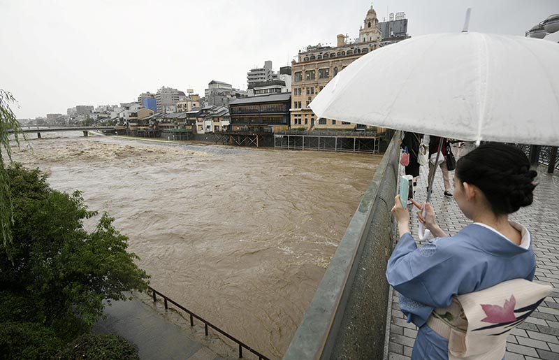 A kimono-clad woman using a smartphone takes photos of swollen Kamo River, caused by a heavy rain, from Shijo Bridge in Kyoto, western Japan, on July 5, 2018.  Photo:  Kyodo/via Reuters