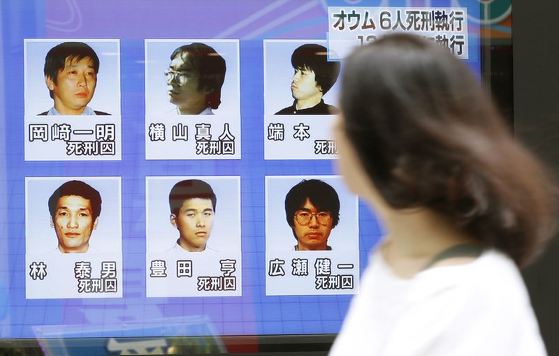 A woman walks on a street while watching TV news reporting executions of six members of Aum Shinrikyo, in Tokyo on Thursday, July 26, 2018. Photo: AP