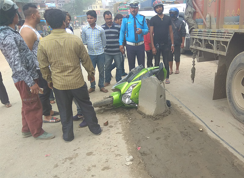 Onlookers and police inspect the scooter and truck involved in the accident in Kalanki, Kathmandu, on Wednesday, July 11, 2018. Photo: Bishal Siwakoti