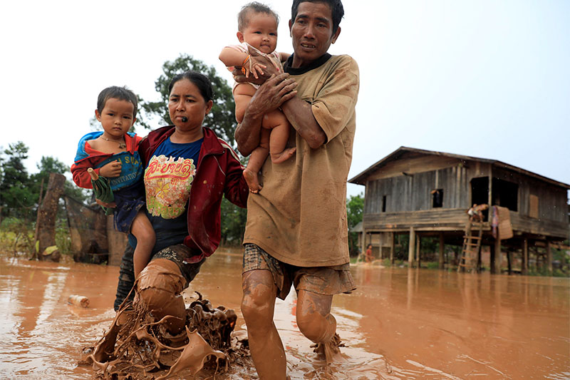 Parents carry their children as they leave their home during the flood after the Xepian-Xe Nam Noy hydropower dam collapsed in Attapeu province, Laos July 26, 2018. Photo: Reuters