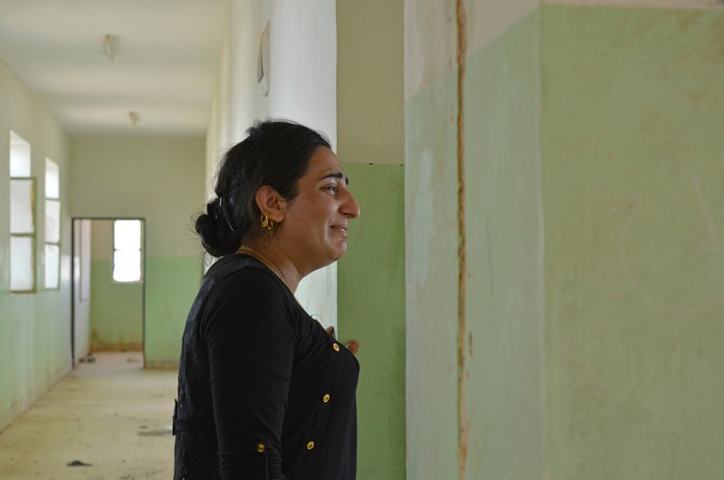 In this photo, provided by Yazda, a U.S.-based Yazidi rights group, Farida Khalaf weeps as she stands inside the schoolhouse where she had been separated from her family and first imprisoned in 2014, by Islamic State militants, in Kocho, northern Iraq on Tuesday, July 3, 2018. Photo: AP