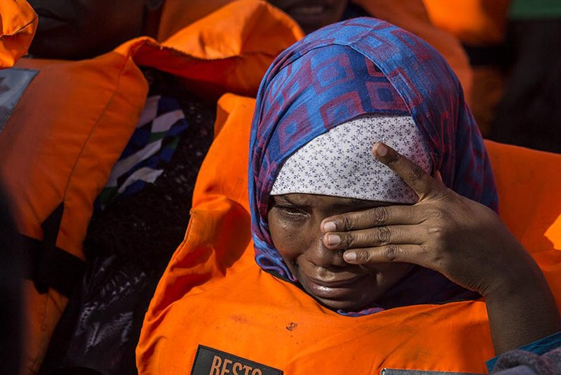RETRANSMISSION TO ADD AP STYLE SIGN-OFF BYLINE - Migrants aboard a rubber dinghy off the Libyan coast wipes her eyes as she waits rescuers aboard the Open Arms aid boat, of Proactiva Open Arms Spanish NGO, on Saturday, June 30, 2018. Photo: AP