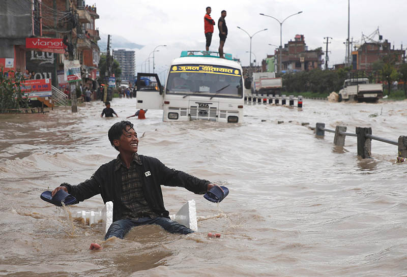 A boy smiles as he uses an improvised raft to maneuver through the floodwater after incessant rainfall in Bhaktapur, on Wednesday, July 12, 2018. Photo: Reuters