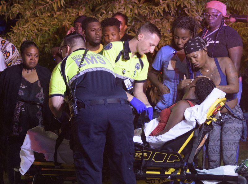 Emergency workers tend to a person that fainted near the scene of a shooting in New Orleans, Saturday night, July 28, 2018. Photo: AP