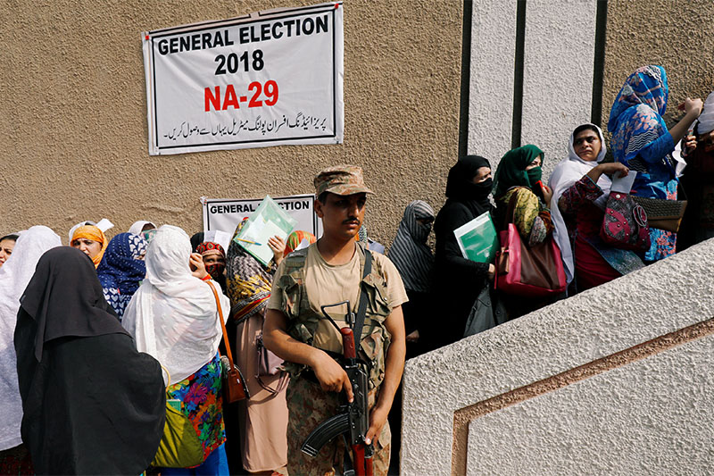Army soldier stands guards where electoral workers gather to collect election materials at distribution point, ahead of general election in Peshawar, Pakistan, on July 24, 2018. Photo: Reuters