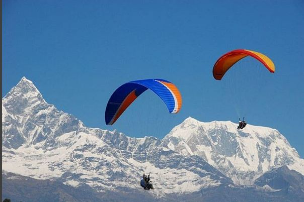 Two Para gliders are seen hovering in the  alluring skies of Pokhara City while Mount Machhapuchre (Fish Tail) shines in the background. Photo: mountainkick.com