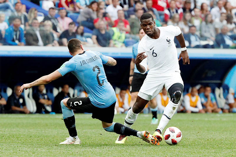 France's Paul Pogba in action with Uruguay's Jose Gimenez. Photo: Reuters