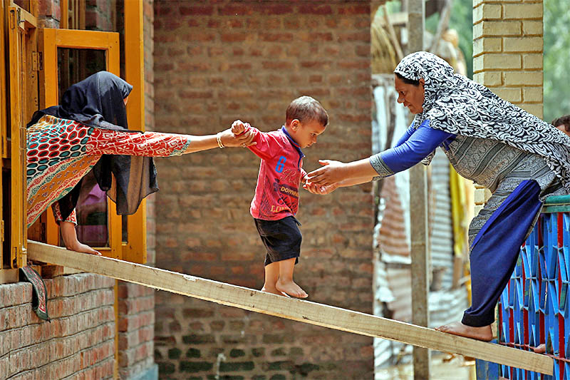Women help a child to cross over to the other house on a wooden plank after flash floods in Tailbal, on the outskirts of Srinagar in India, on Tuesday, July 24, 2018. Photo: Reuters