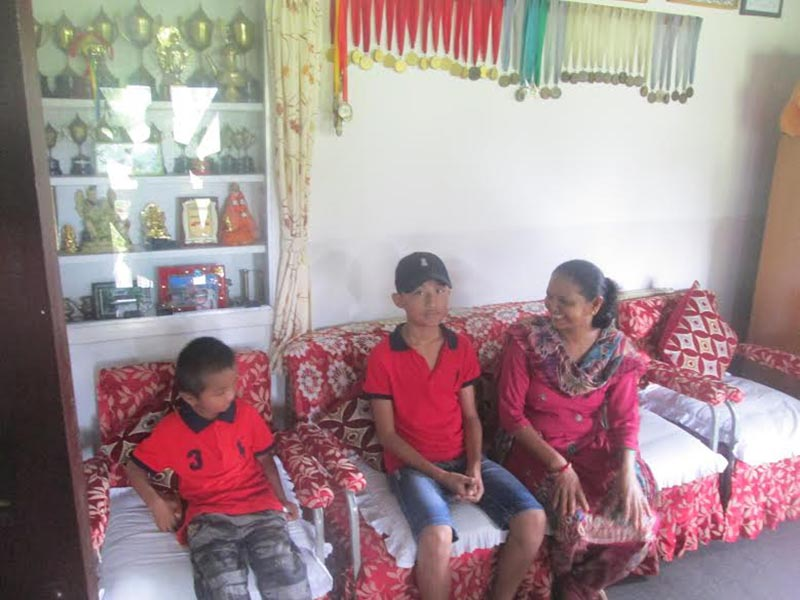 Parbati Pandey of Gurans House at SOS Hermann Gmeiner School taking the responsibility of bringing up two orphan siblings Bibash and Bishesan after their parents died in a tipper accident in Mustang a few days ago, in the school at Ram Bazaar, Pokhara, on Tuesday, July 24, 2018. Photo: THT