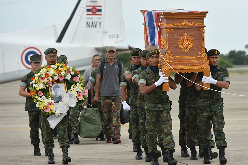 An honour guard carries the coffin of Samarn Kunan, 38, a former member of Thailand's elite navy SEAL unit who died working to save 12 boys and their soccer coach trapped inside a flooded cave, at an airport in Rayong province, Thailand, July 6, 2018. Photo: Reuters