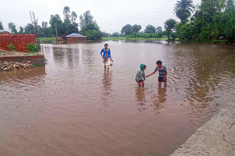 A woman and kids seek safe shelter after heavy rains and lack of proper drainage system inundated their house in Mahakali Municipality, Kanchanpur. Photo:RSS