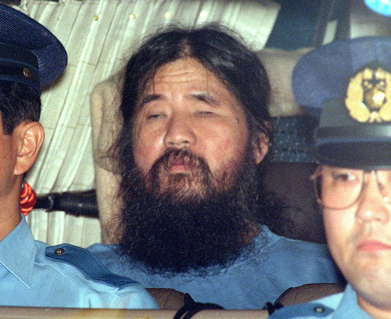 File - In this photo, Japanese doomsday cult leader Shoko Asahara, center, sits in a police van following an interrogation in Tokyo on Sept. 25, 1995. Photo: AP