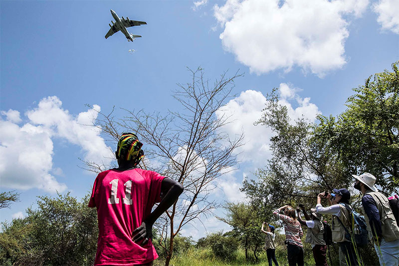 People watch as a plane air drops UN's World Food Programme (WFP) food aid near the town of Katdalok, in Jonglei State of South Sudan, on July 30, 2018. Photo: Reuters