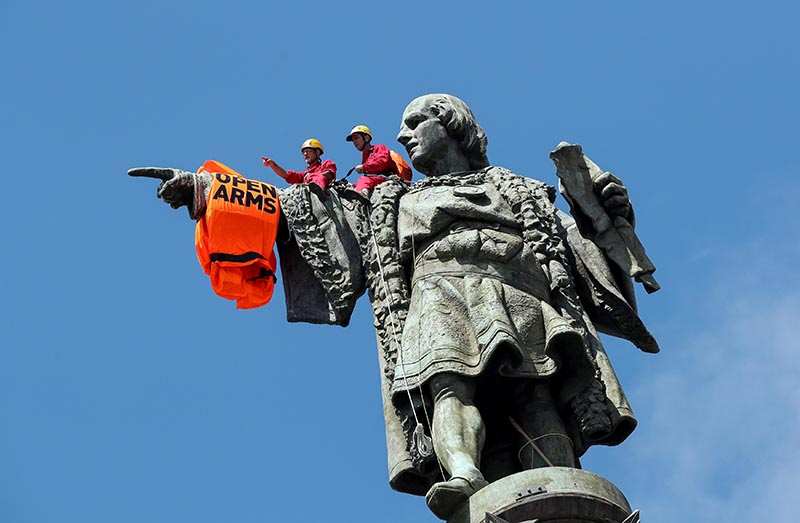 Activists from the Spanish Proactiva Open Arms charity place a life jacket on the Christopher Columbus statue after the Open Arms rescue boat arrived at a port in Barcelona, Spain, carrying migrants rescued off Libya, July 4, 2018. Photo: Reuters