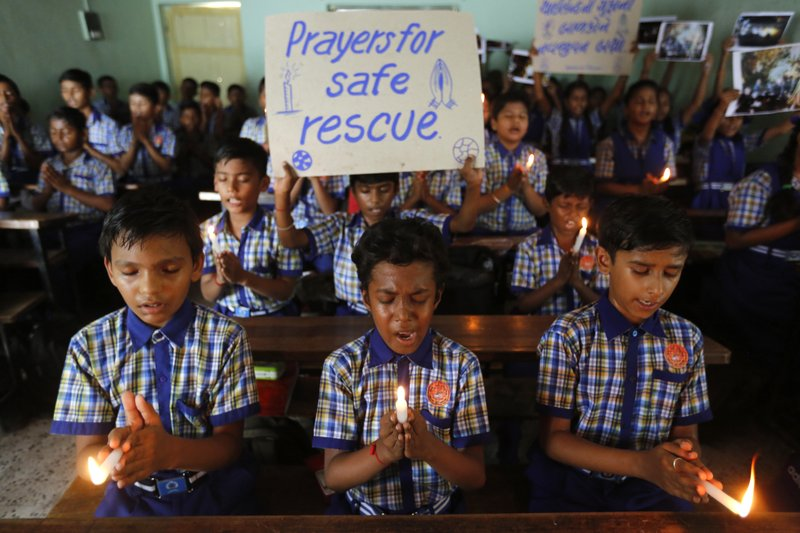 File - In this photo, students at a school in Ahmadabad, India, hold candles and pray for a group of Thai youth soccer players and their coach who have been trapped since June 23, in Mae Sai, Chiang Rai province, northern Thailand on July 9, 2018. Photo: AP