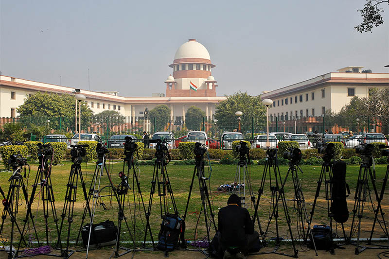 FILE PHOTO: A television journalist sets his camera inside the premises of the Supreme Court in New Delhi February 18, 2014. Photo: Reuters