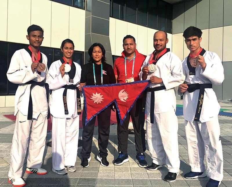 Nepali taekwondo players pose for a photo with coaches Deepak Bista and Sangina Baidya in Pohang, South Korea on Wednesday.