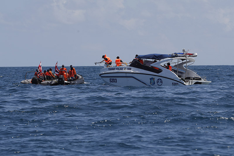 Thai rescue divers and a tourist police boat are seen during a search mission for missing passengers from a capsised tourist boat in the water off Phuket, in Thailand, on Saturday, July 7, 2018. Photo: AP