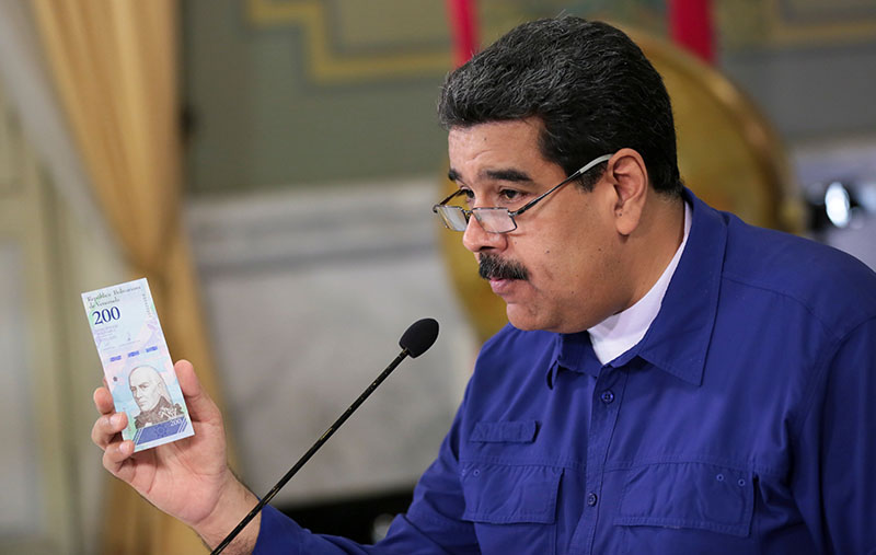Venezuela's President Nicolas Maduro holds a bank note of the new Venezuela's currency Bolivar Soberano (Sovereign Bolivar) as he speaks during a meeting with ministers at Miraflores Palace in Caracas, Venezuela July 25, 2018. Miraflores Palace/Handout via Reuters