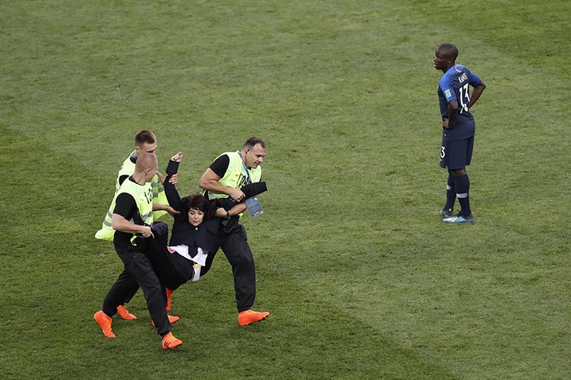 France's Ngolo Kante watches as a woman is dragged away by stewards after running into the pitch during the final match between France and Croatia at the 2018 soccer World Cup in the Luzhniki Stadium in Moscow, Russia, Sunday, July 15, 2018. Photo: AP