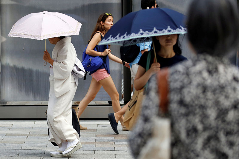 A kimono-clad woman using a sun umbrella walks on a street during a heatwave in Tokyo, Japan July 23, 2018.  Photo: Reuters
