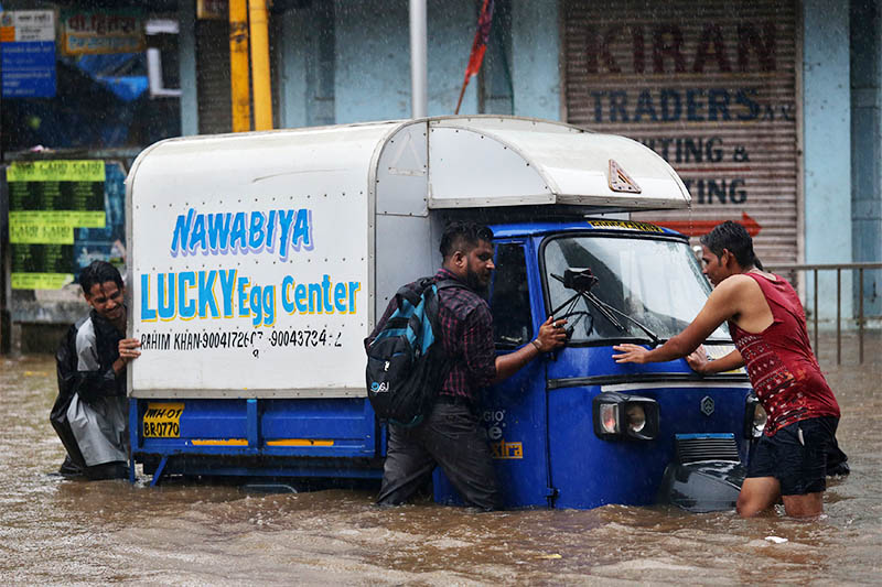 People push a tempo after it broke down at a waterlogged street after heavy rains in Mumbai, India July 3, 2018. Photo: Reuters
