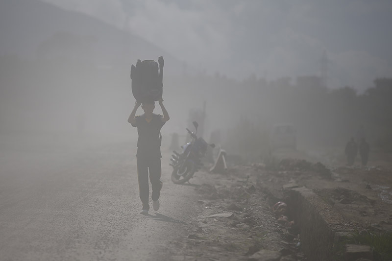 FILE: A boy uses his jacket to cover himself as he walks along a dusty road, in Kathmandu, on Tuesday, August 07, 2018. Photo: Skanda Gautam/THT