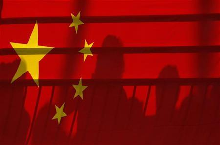 The shadows of spectators are seen through a Chinese national flag during the men's kayak (K1) semifinal at the Beijing 2008 Olympic Games August 12, 2008.     REUTERS/Phil Noble
