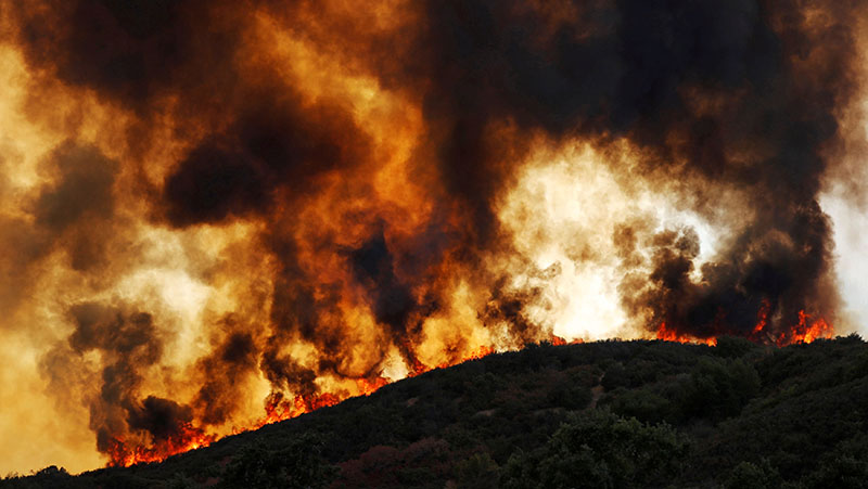 Wind-driven flames roll over a hill towards homes during the River Fire (Mendocino Complex) near Lakeport, California, US, on August 2, 2018.