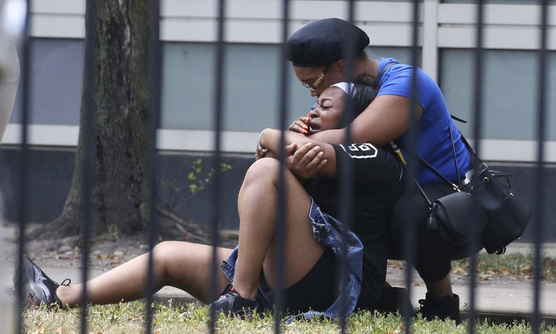 In this photo, two women cry outside the Stroger Hospital in Chicago, after they were asked to leave due to overwhelming crowds of family and friends of shooting victims on  Sunday, Aug. 5, 2018. Photo: AP