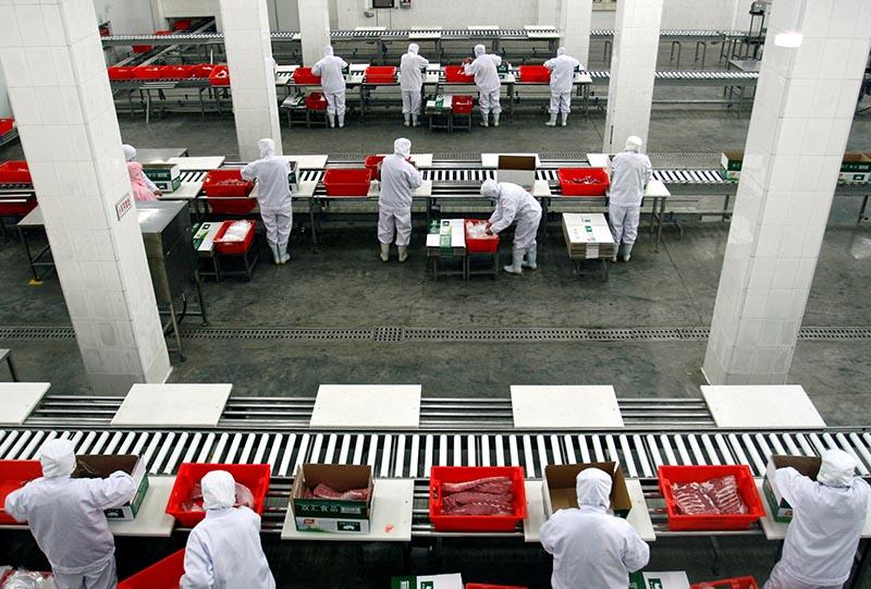 Employees sort cuts of fresh pork inside a Shuanghui factory in Zhengzhou, Henan province, China, on March 15, 2013. Photo: Reuters