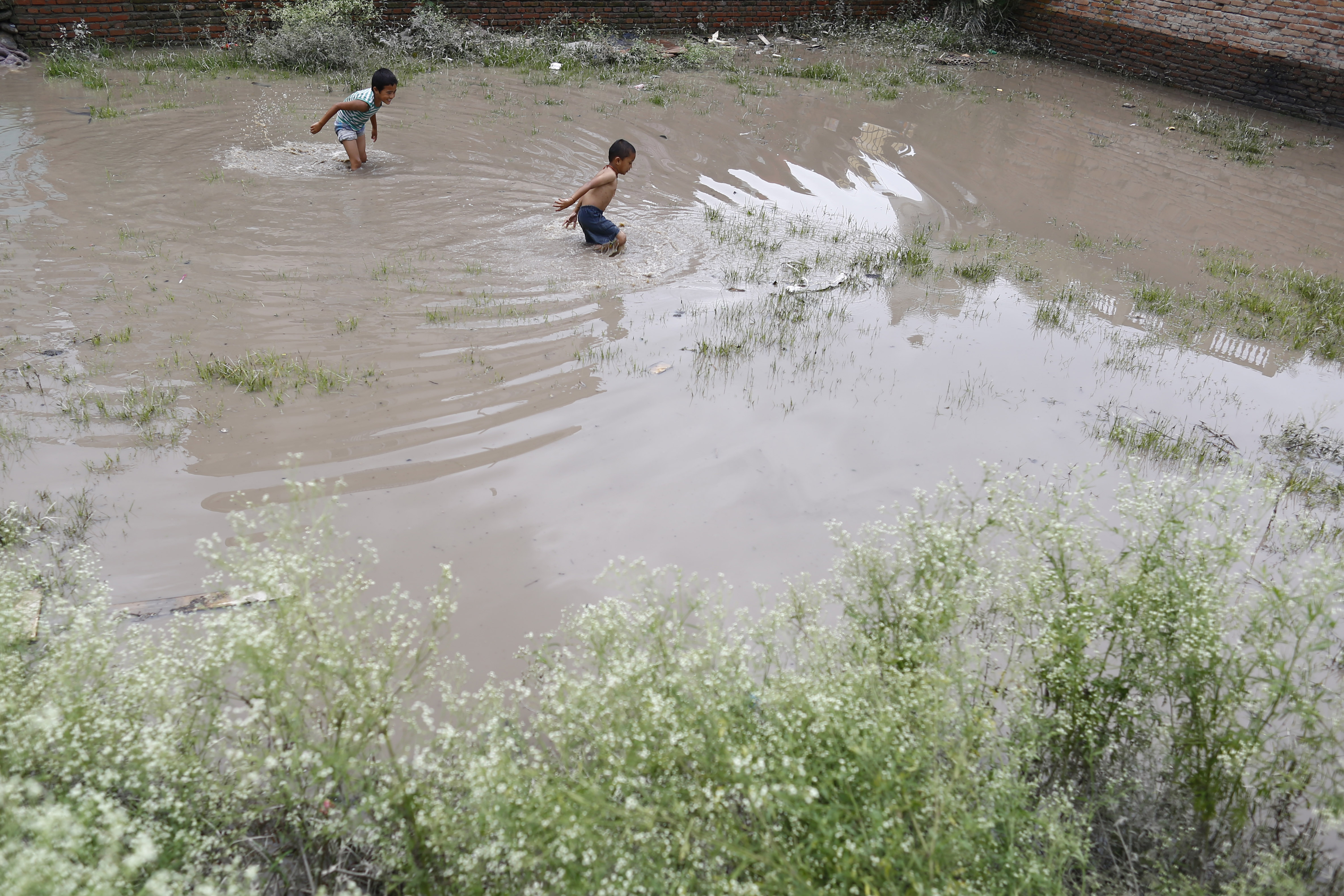 Kids play in a flooded patch of land after  water from swelled Dhobikhola river entered settlements in Kathmandu, Nepal on Wednesday, August 15, 2018.