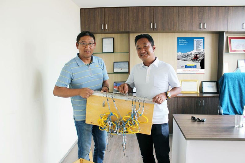 Search equipment being handed over by Captain Ashish Sherchan (right) to Pemba Gyaltsen Sherpa.