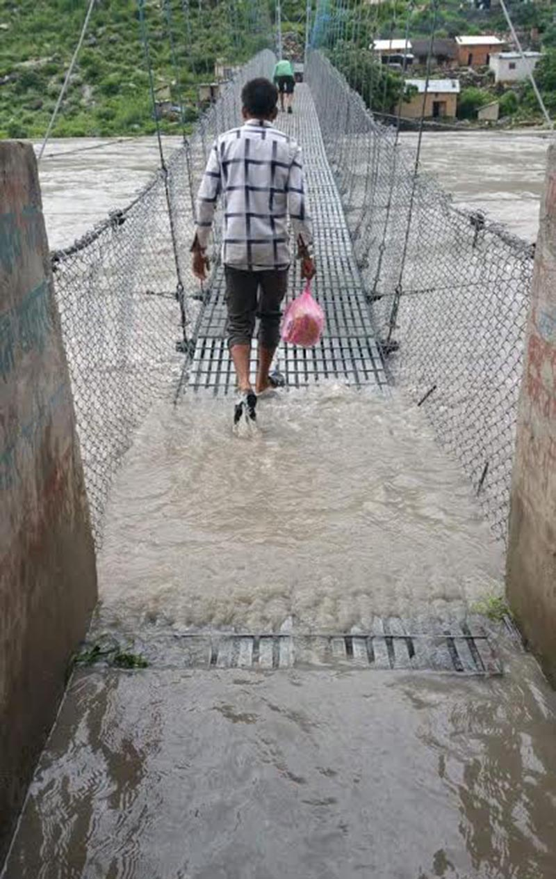 People crossing the bridge over Karnali River, in Bajura, on Sunday, August 26, 2018. Photo: THT