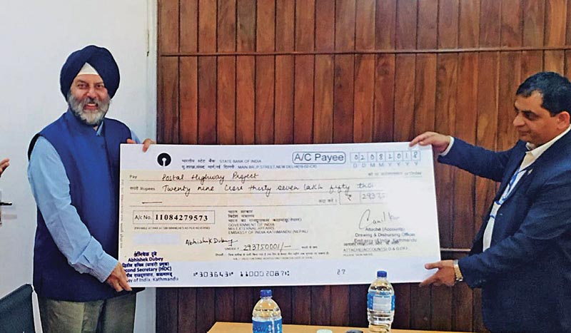 Indian Ambassador Manjeev Singh Puri handing over a cheque to Secretary at the Ministry of Physical Infrastructure and Transport Madhusudan Adhikari, in Kathmandu, on Tuesday, August 14, 2018. Photo: THT