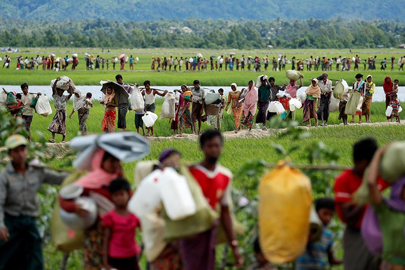 File - Rohingya refugees, who crossed the border from Myanmar two days before, walk after they received permission from the Bangladeshi army to continue on to the refugee camps, in Palang Khali, near Cox's Bazar, Bangladesh, on October 19, 2017. Photo: Reuters