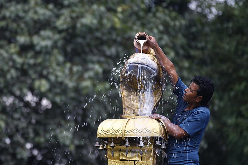 A man pours milk on the idol of the snake on the day of Nag Panchami festival at Nagpokhari in Naxal, Kathmandu, on Thursday, August 16, 2018. Hindus across the country and abroad celebrate Nag Panchami, by worshipping snakes. Photo: Skanda Gautam/THT