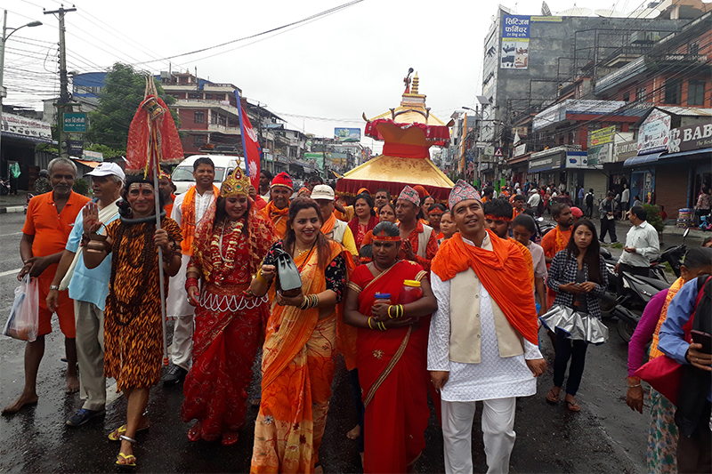 Hindu devotees along with a couple disguised as Hindu deities 'Mahadev-Parvati', march on the road, heading to offer water to 'Shiva Linga,' an idol at Kedareshwar Mahadev temple at Baidam in Pokhara Metropolitan City-6, to mark the conclusion of Shrawan Sombar festival, on Monday, August 13, 2018. On the last Monday of the month 'Shrawan' in Nepali calendar, Hindus offer prayers and water brought from local Seti River at Gaighat. Photo: Rishi Ram  Baral