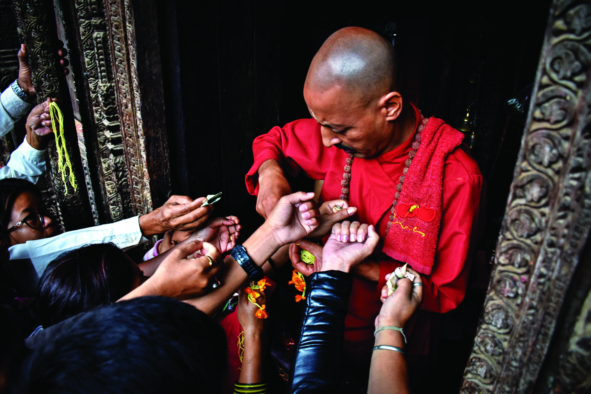 Devotees getting sacred thread tied around their wrists from a priest at Kumbheshwor temple in Lalitpur. Photo: THT