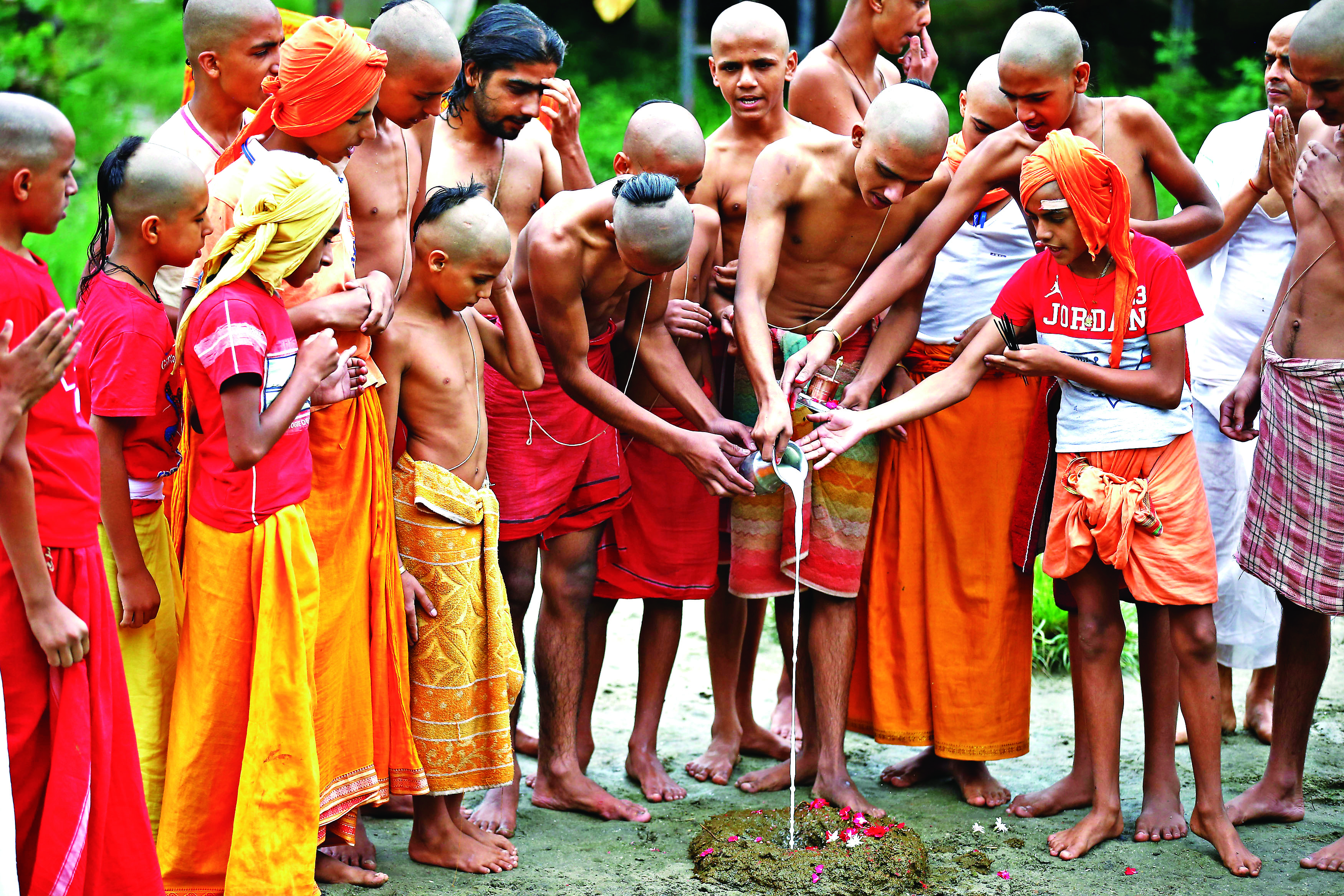 Nepali young Hindu priests perform rituals during Janai Purnima or Sacred Thread festival inside Pashupathinath Temple in Kathmandu, Nepal on Sunday, August 26, 2018. It is believed that tying the sacred thread rids skin diseases.
