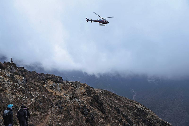 FILES- Hikers walking on a trail as a helicopter comes in to land at Mong La village near Namche Bazar on the route to reach Everest Base Camp. Photo: AFP