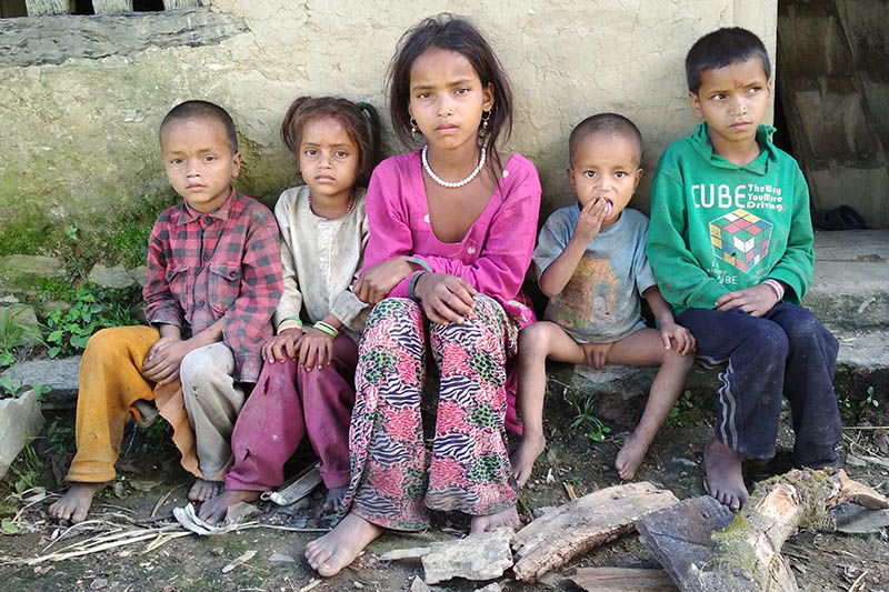 Parbati Saud (centre) along with her siblings pose for a portrait in front of their house in Bajura. Photo: Prakash Singh