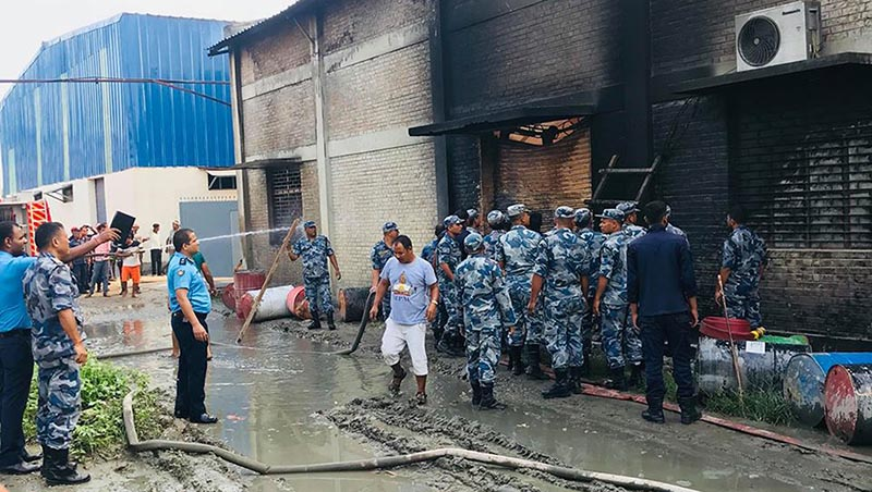 Security personnel inspecting to break off a wall to enter into 'Makalu Soap and Industries' located on the premises of Amrit Vanaspati Ghee Industry in Chainpur area of Parwanipur Rural Municipality-3, in Bara district, on Monday, September 17, 2018. The industry caught fire this morning and the effort is ongoing to bring the blaze under control. Photo: Ram Sarraf/THT