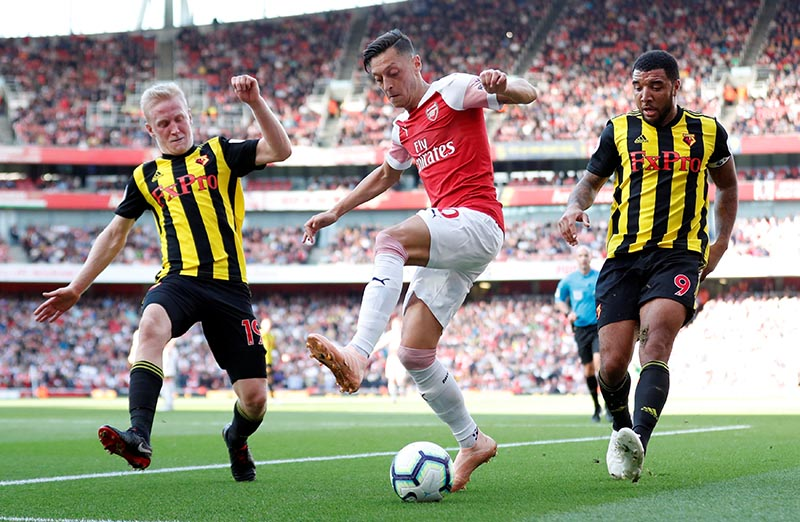 Arsenal's Mesut Ozil in action with Watford's Will Hughes and Troy Deeney during Premier League match between Arsenal and Watford, at  Emirates Stadium, in London, Britain, on September 29, 2018. Photo: Action Images via Reuters