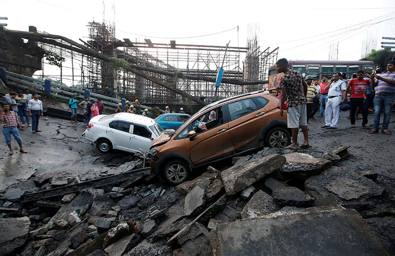 People stand next to the wreckage of vehicles at the site of a bridge that collapsed in Kolkata, India, on September 4, 2018. Photo: Reuters
