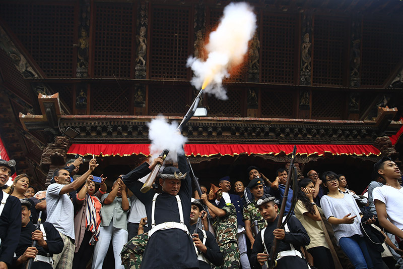 A Nepal Army personnel fires a shot marking the beginning of the eight-day long 'Indra Jatra' festival, celebrated to honour Indra, King of Heaven and God of rain and harvest, in Hanumandhoka, Kathmandu, on Friday, September 21, 2018. Photo: Skanda Gautam/THT