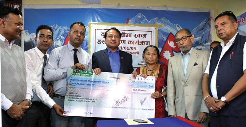 NSC Member Secretary Keshab Kumar Bista handing over cheque to Maiya Maharjan Shrestha, mother of deceased cyclist Narayan Gopal Maharjan, in Kathmandu. Photo: THT