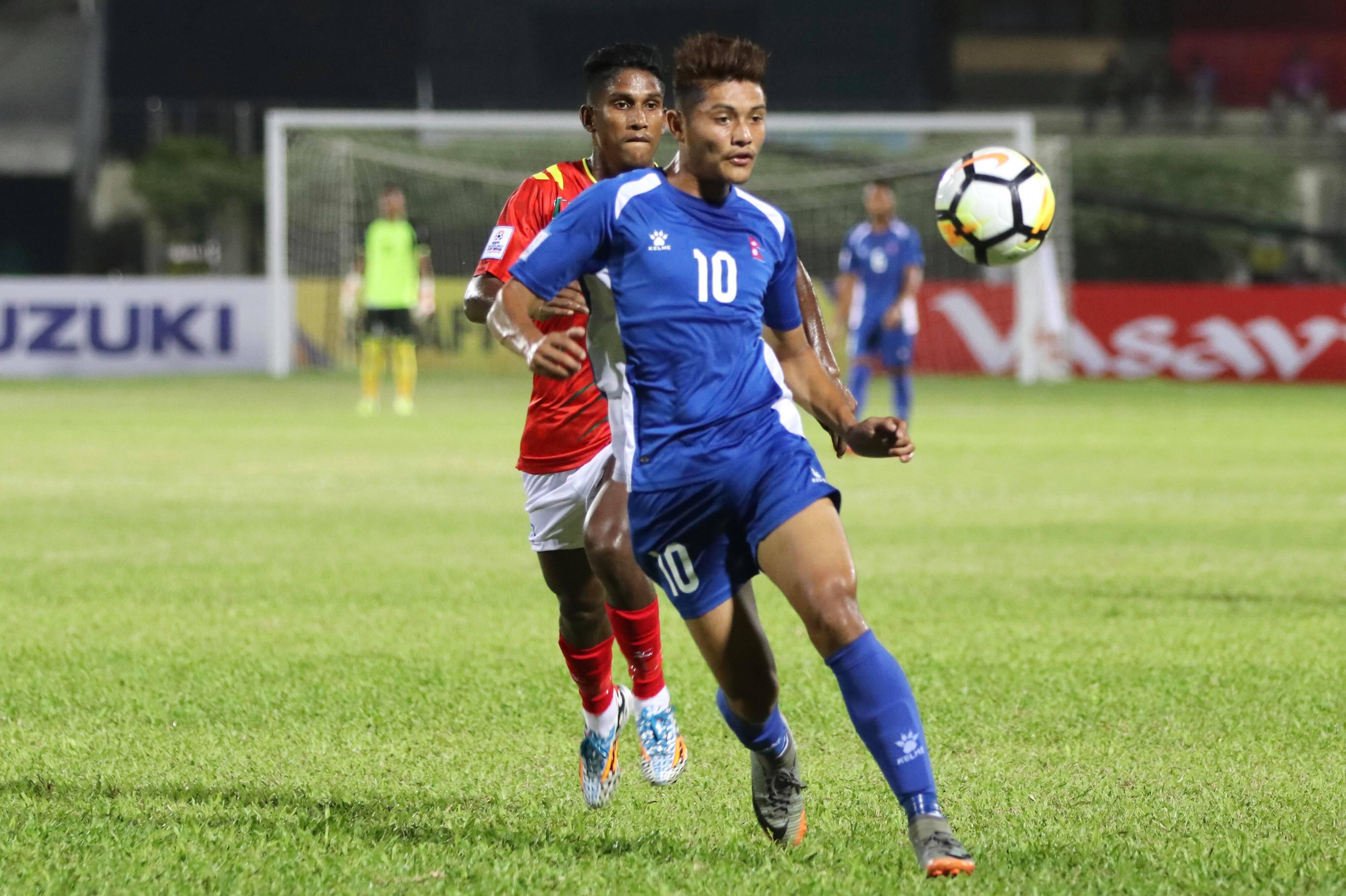 Nepalu2019s Bimal Gharti Magar (front) beats past a Bangladesh player during their Group A match of the SAFF Championship at the Bangabandhu National Stadium in Dhaka on Saturday, September 8, 2018. Photo: THT