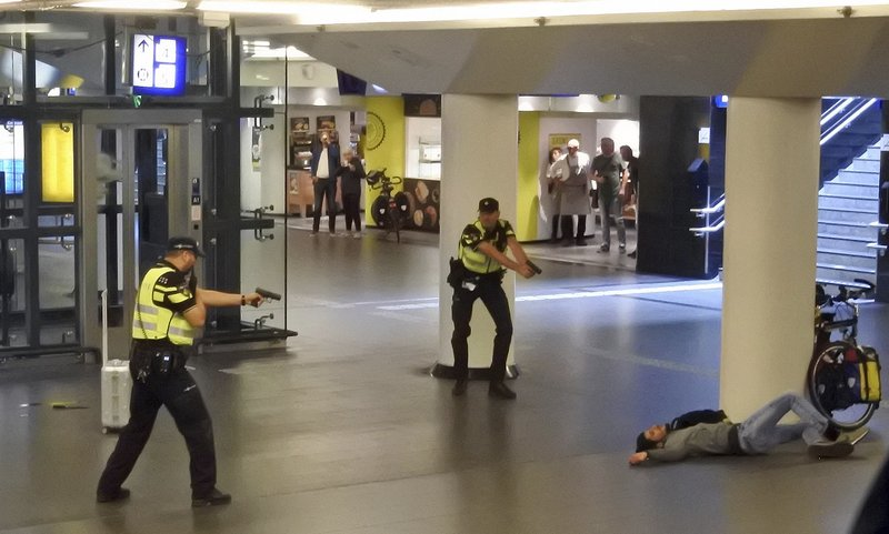 Dutch police officers point their guns at a wounded 19-year-old man who was shot by police after stabbing two people in the central railway station in Amsterdam, the Netherlands, on Friday Aug. 31, 2018. Photo: AP